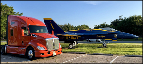 A Kenworth T680 poses for a photo with a Boeing F18 Hornet of the US Navy Blue Angels Demonstration Squadron while at NAS Pensacola