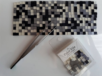 Mosaic made with tiny glass tiles, with tweezers to show size.