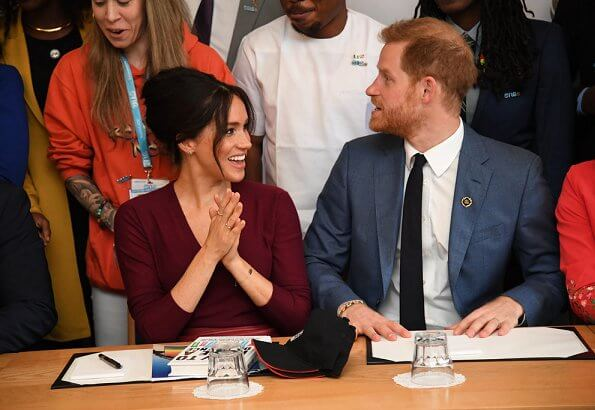 Meghan Markle wore Joseph pullover, Hugo Boss Selrita leather skirt, Sarah Flint pumps and Emily Mortimer Hera gold and diamond earrings