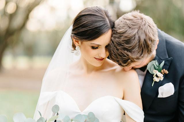 groom kissing brides shoulders