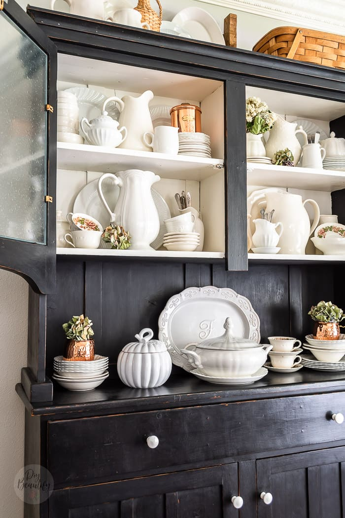 black vintage hutch filled with white ironstone dishes, copper accents, dried hydrangeas and vintage pattern teacups