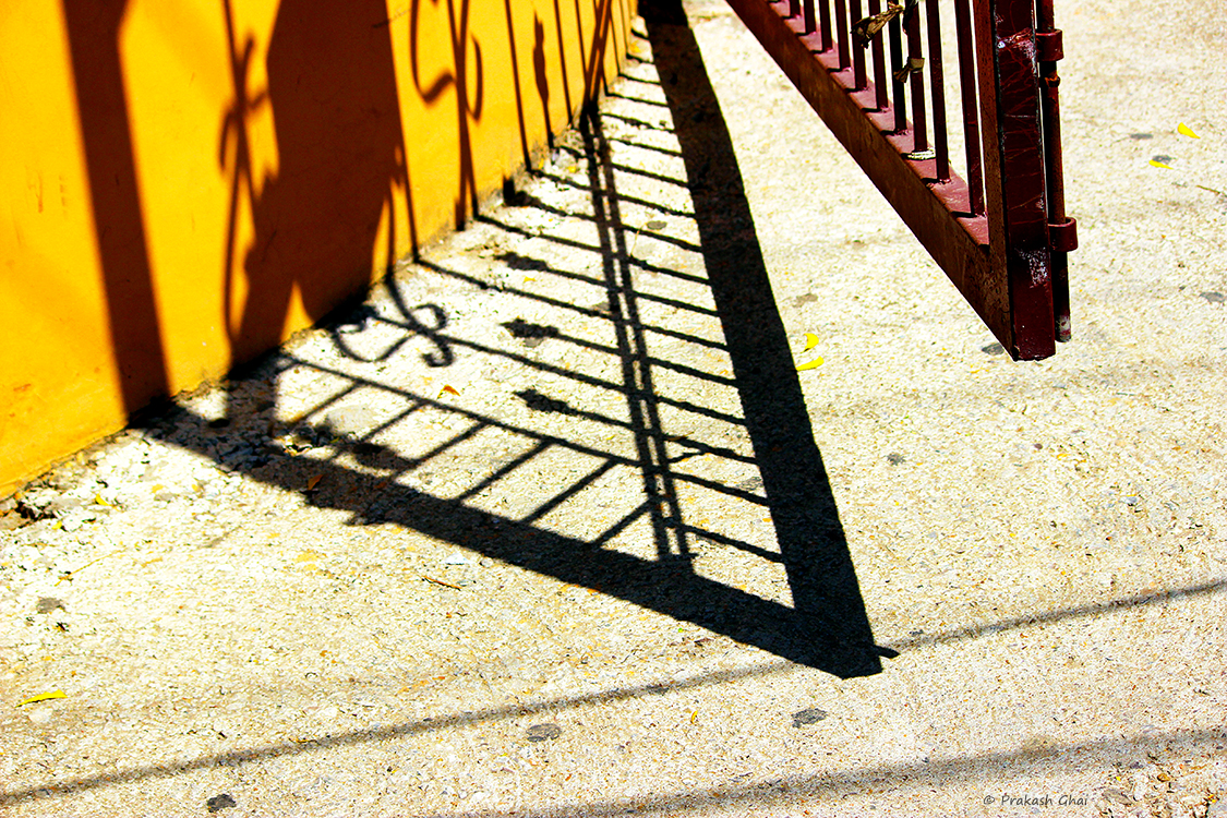 A minimalist photo of the Shadow of a Gate partially open