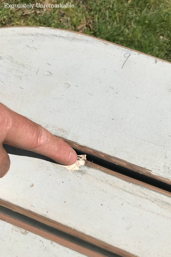 A finger applying wood putty to cracks in the wood of a bench