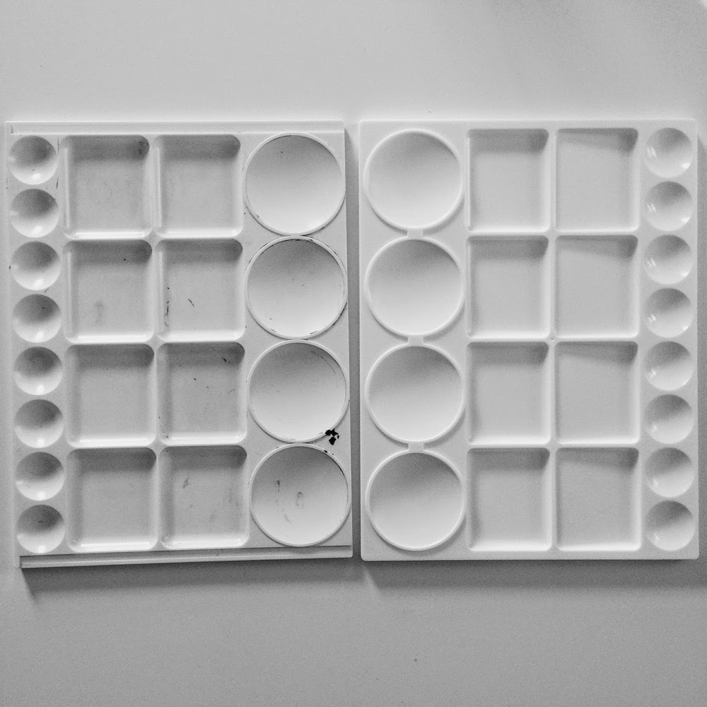black and white photo of two empty paint palettes