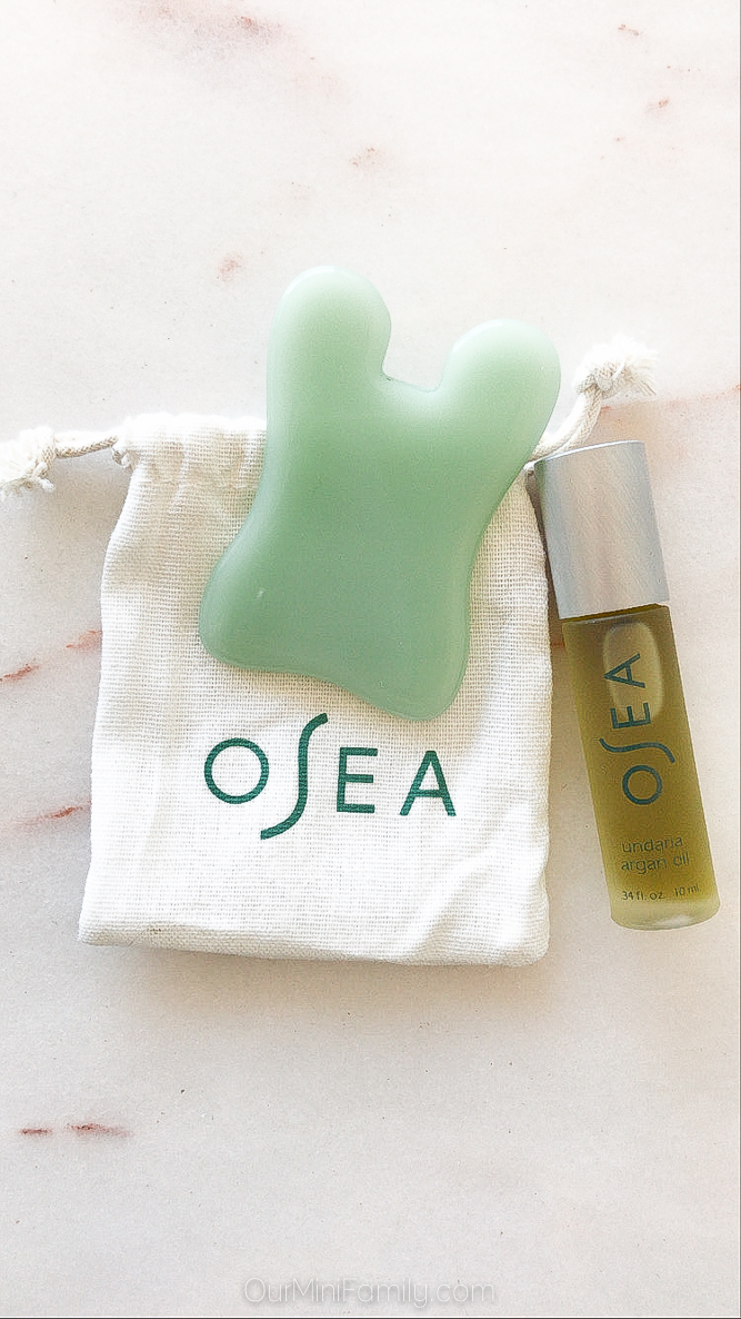 OSEA green gua sha tool and small bottle of oil sitting on top of white marble
