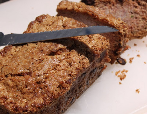 This is a photo a classic zucchini bread with walnuts and raisins being sliced