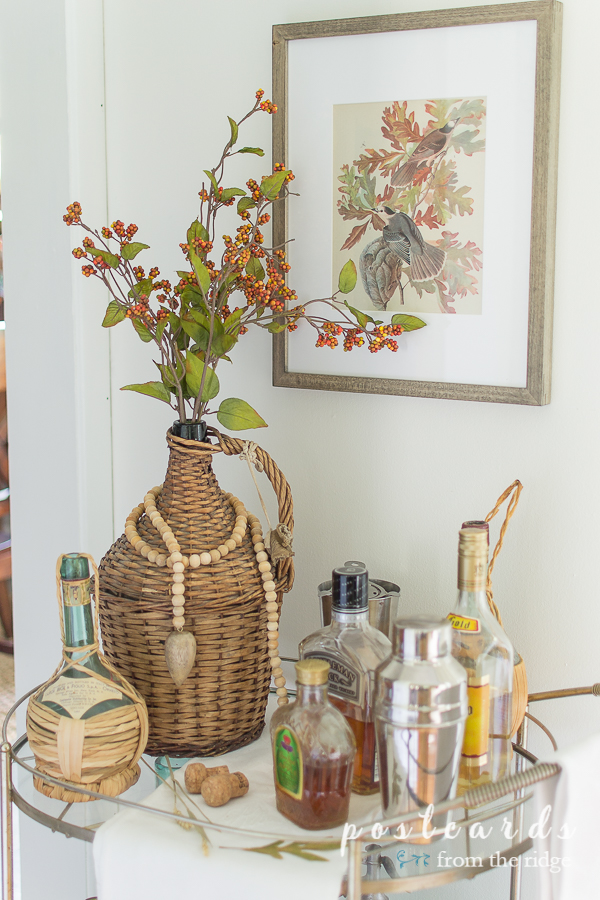 wicker demijohns and liquor on mid century modern bar cart