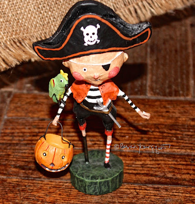 This photo features an whimsical figurine depicting a trick or treater dressed in a Pirate costume.