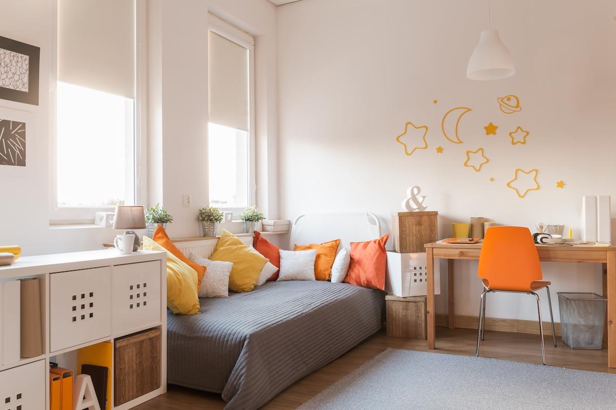 Habitación infantil pintada de blanco con textiles en amarillo y naranja