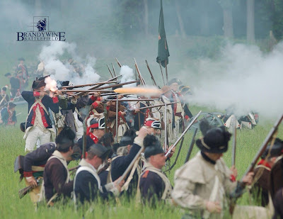 Revolutionary War era reenactors in formation, firing muskets.