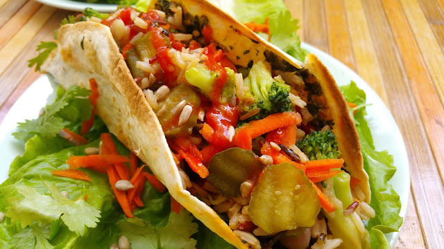 Tacos rellenos de judías, arroz y verduras con salsa de aguacate y cilantro