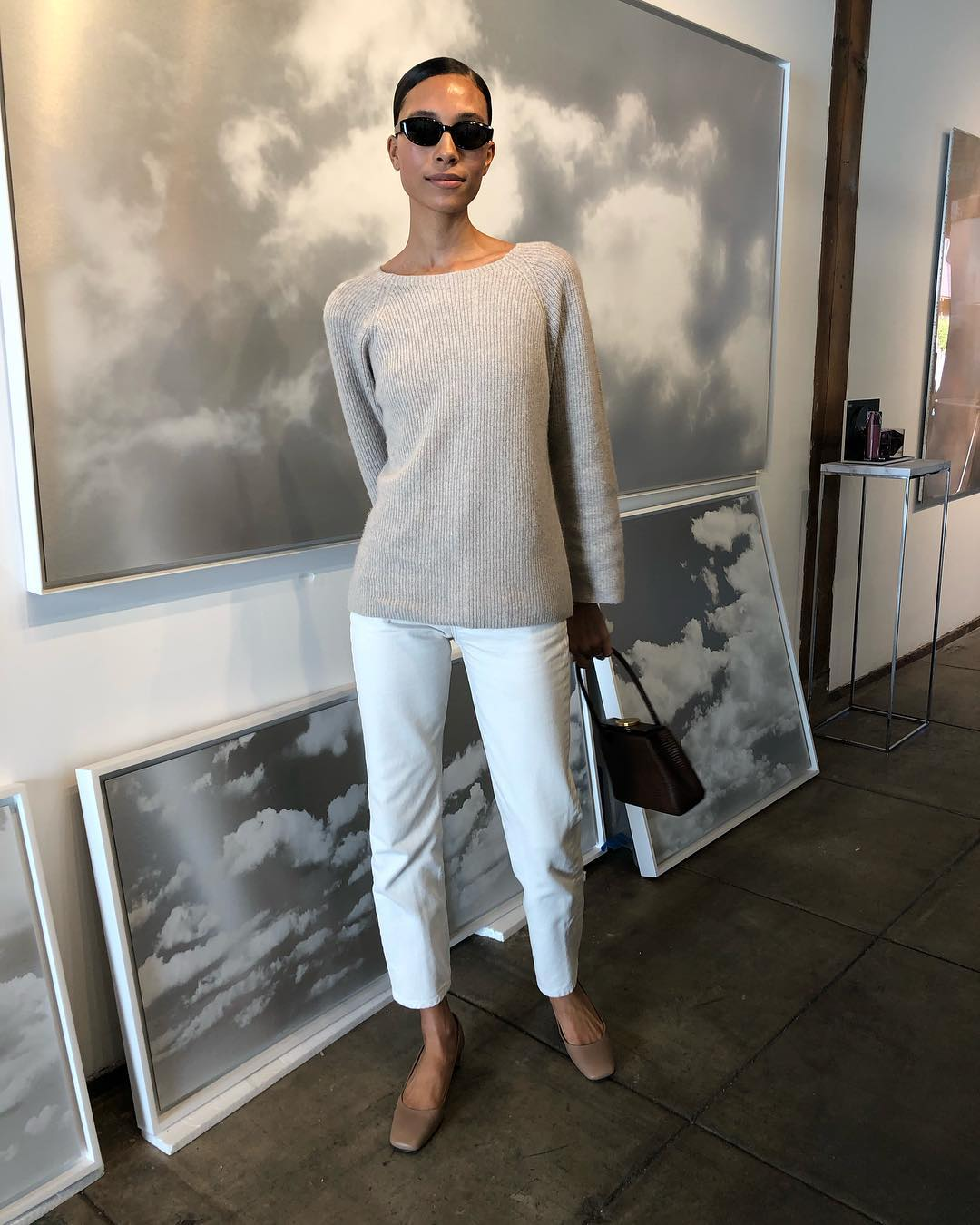 Neutral Spring Outfit Inspiration — Tylynn Nguyen in black cat-eye sunglasses, a biege sweater, white jeans, and tan square-toe shoes