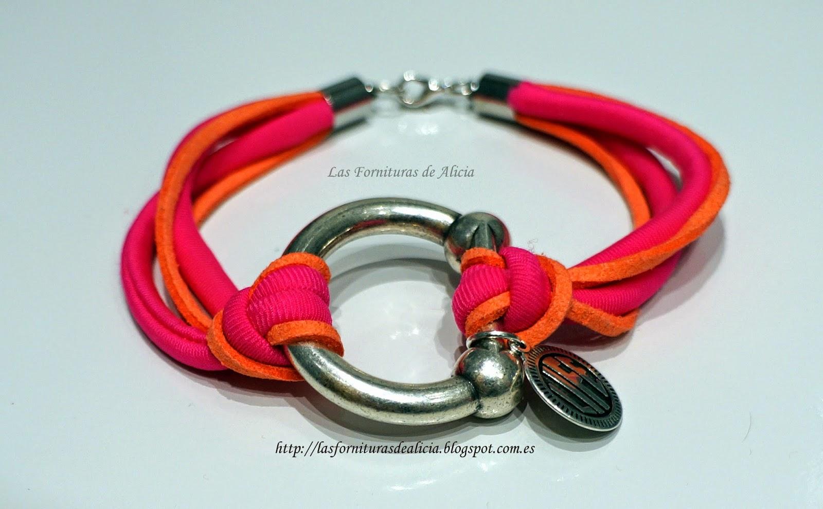 870e046489fc DESCRIPCIÓN  Pulsera hecha con cinta de lycra rosa y antelina anudados a  una pieza central plateada de zamak( ) con forma de estribo y colgante