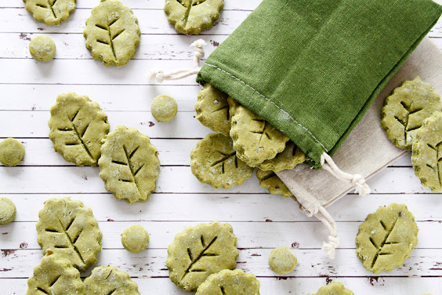 Homemade dog treats shaped like green leaves with a green drawstring treat bag