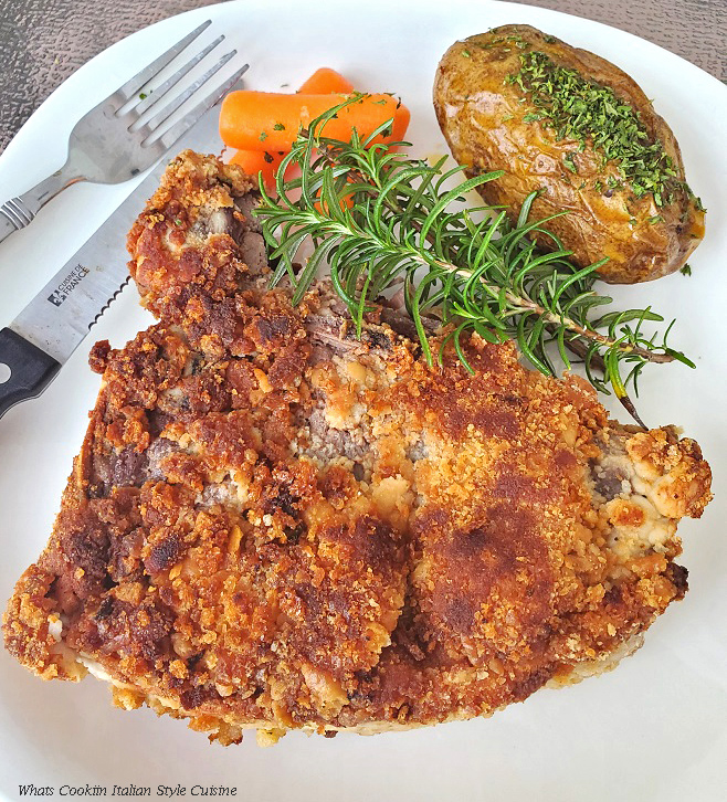 This is a t bone steak coated with an Italian flavored cracker crumb on a white plate with baked potato and steamed carrots. There is also a sprig of rosemary on the plate