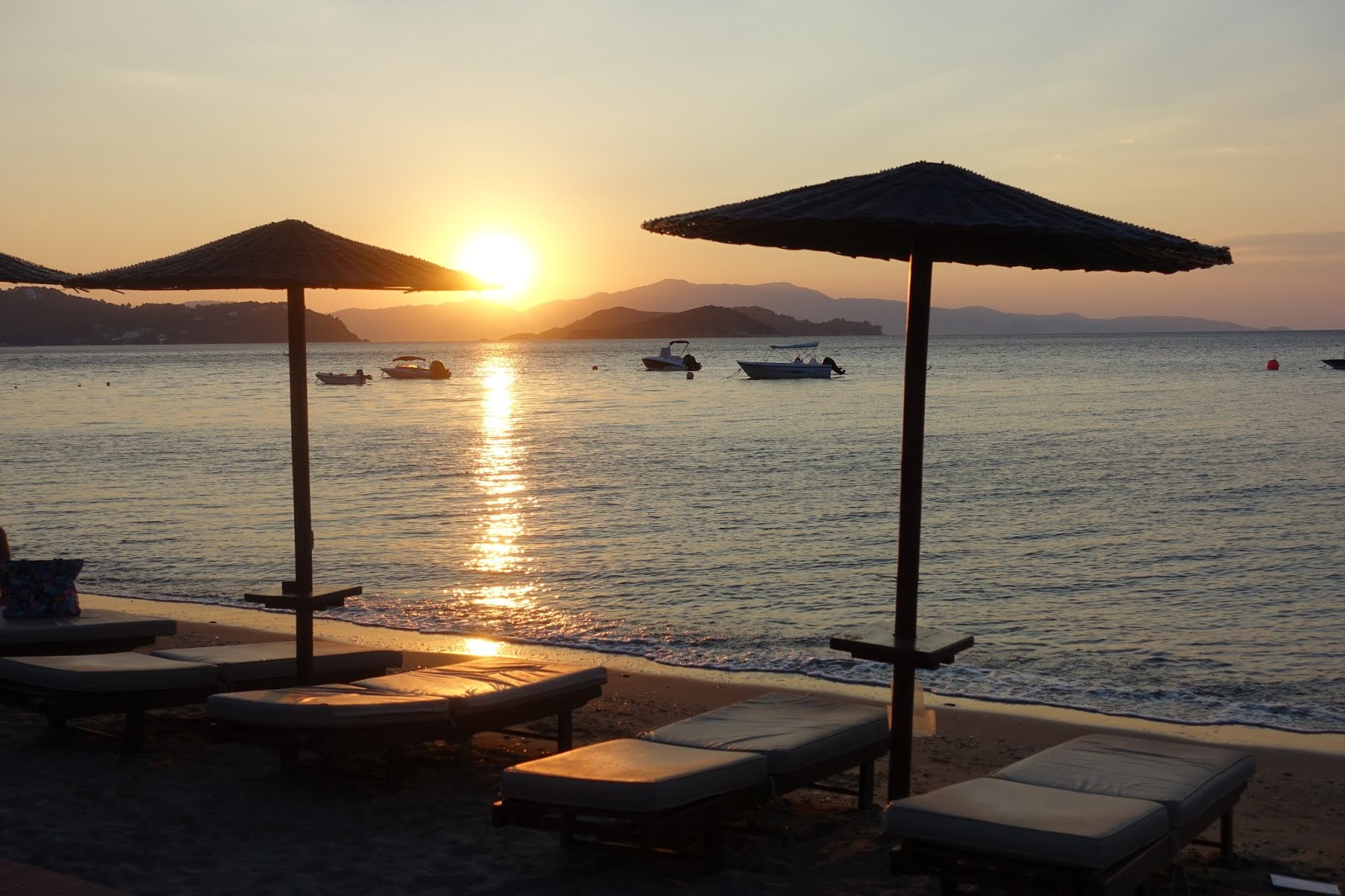 The sun comes up over the sunbeds at Vassilias beach, Skiathos in Greece