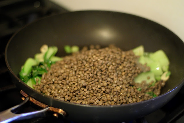 The lentils being added to the frying pan with the bok choy, green onions, and garlic.