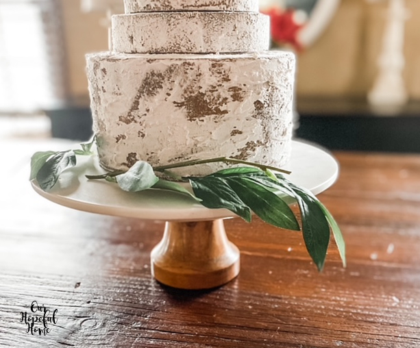 bottom layer fake naked cake white icing green leaves