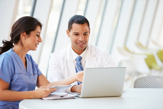 Nurse and doctor looking at a computer screen