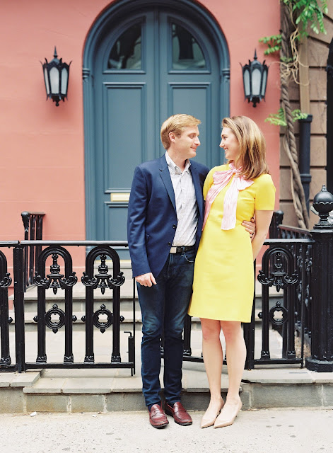 Liz smiles at Ted in front of a blue doorway in Greenwich Village Engagement Portraits
