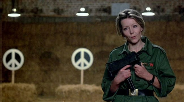 Ingrid Pitt on a firing range holding a sub machine gun