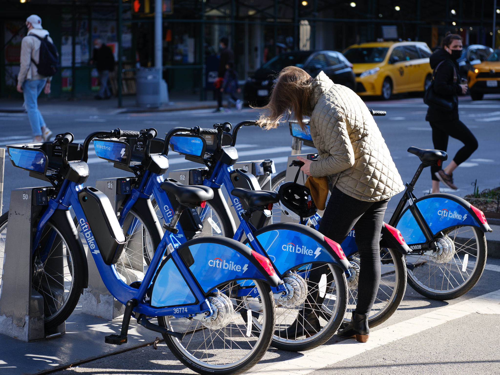 a photo of a young woman renting a citibike in new york city