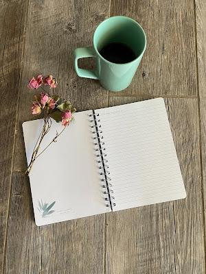 Diario con una flor y una taza de café