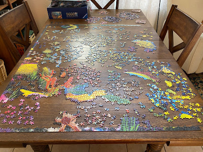 Photo of a partially done puzzle covering an entire dining room table