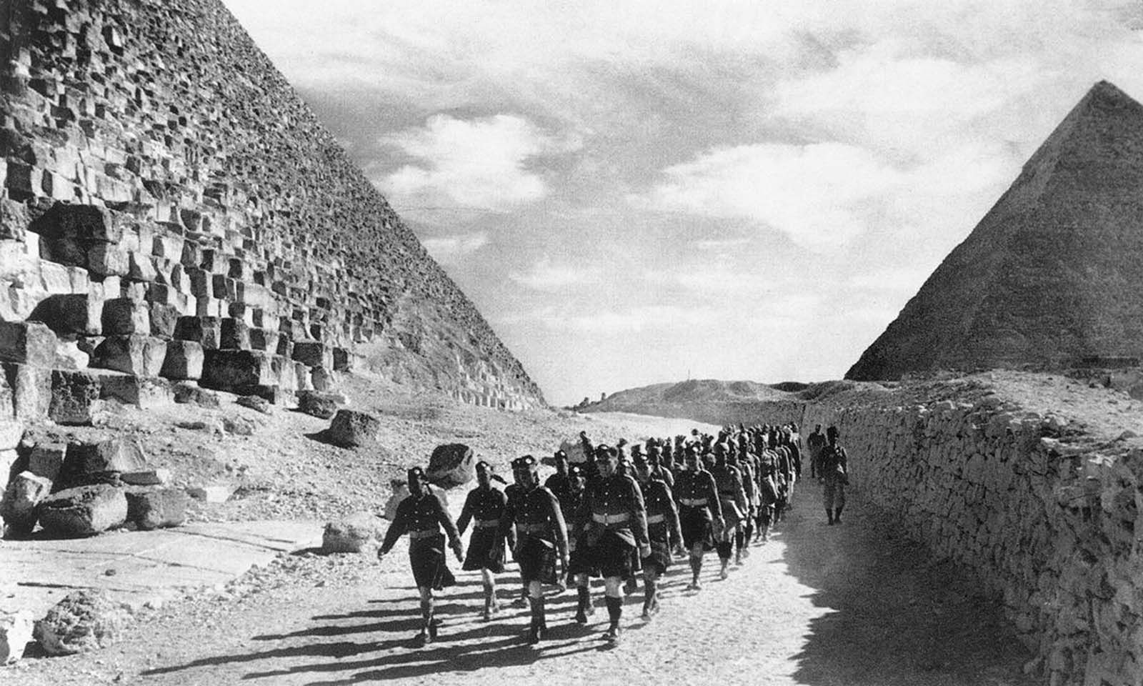 Cameron Highlanders, a Scottish infantry regiment of the British Army, and Indian troops march past the Great Pyramid in the North African Desert, on December 9, 1940.