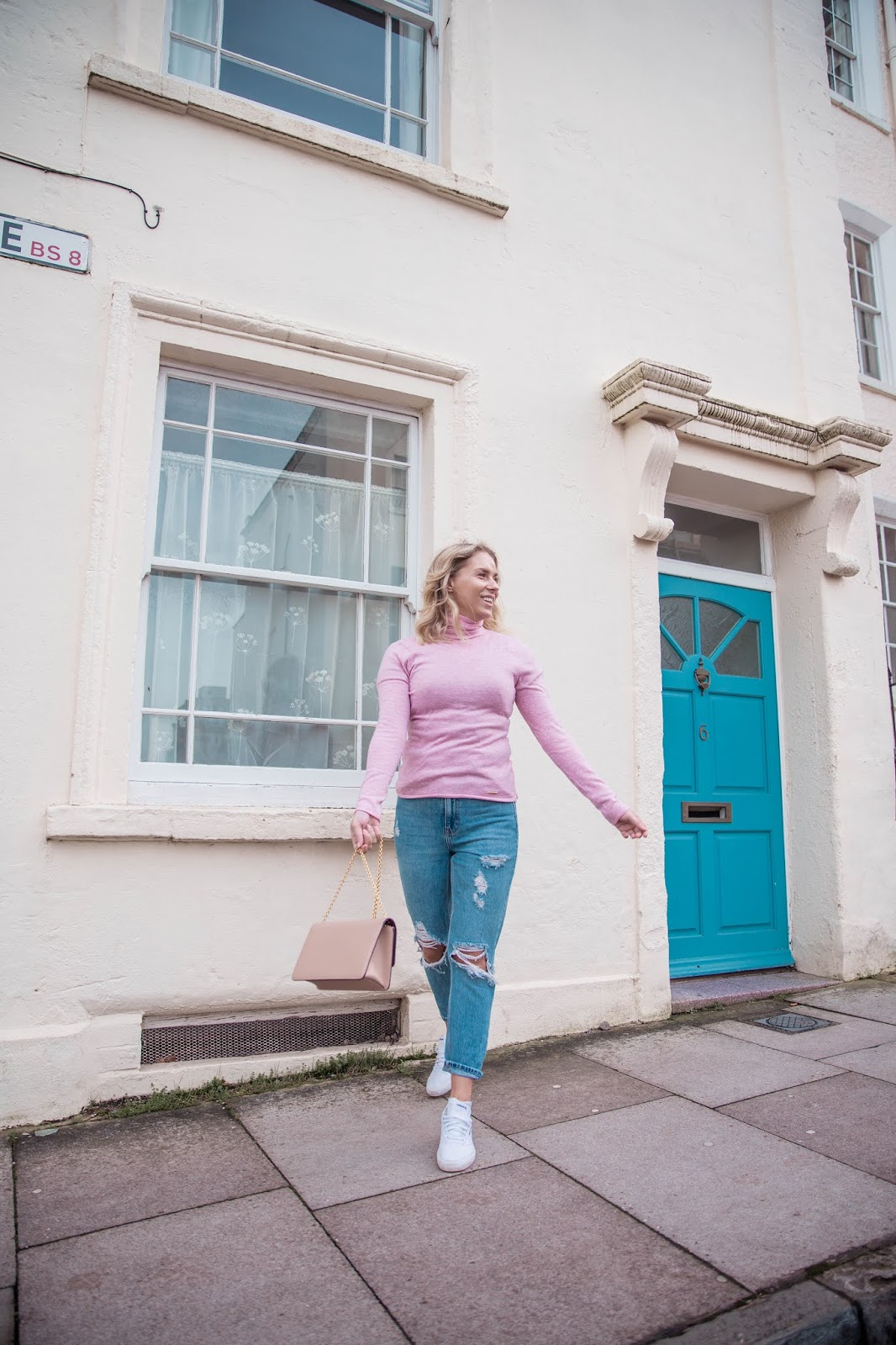 Rachel Emily outside a cream house with a blue door smiling widely