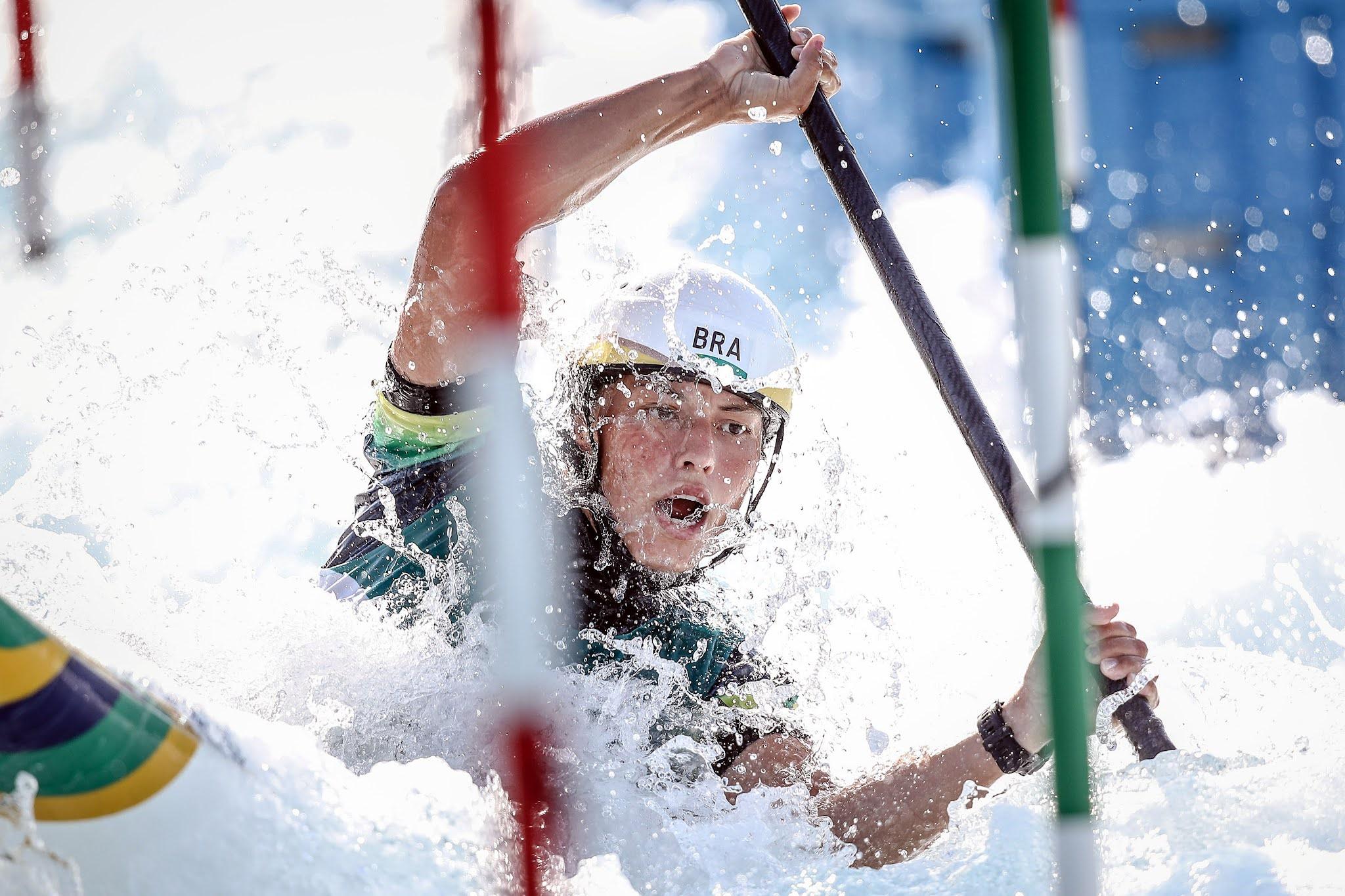 Ana Sátila competindo na canoagem slalom; ela está entre portas, com o remo na mão, de capacete, e com a água cobrindo a foto
