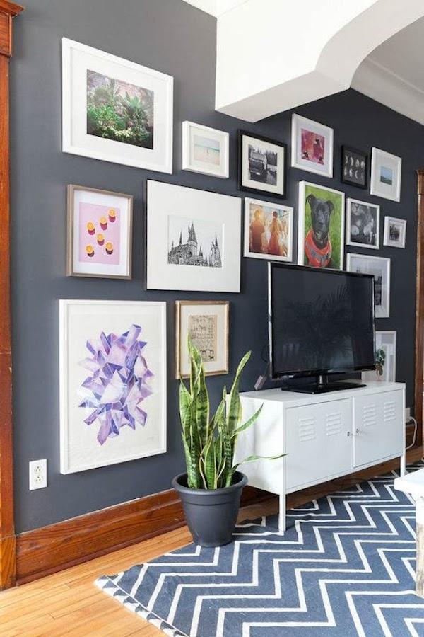 Tv plana con pared negra al fondo y colección de cuadros