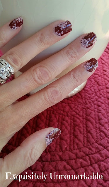Hand wearing diamond wedding rings and floral red nail wraps