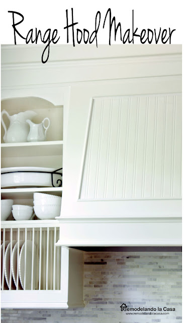 white range hood with beadboard detail and plate rack inside cabinet full of white dishes and cups