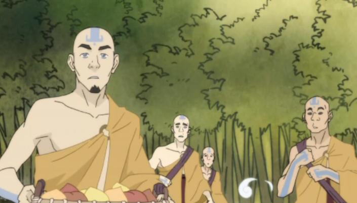 Imagem: vários nômades do ar, homens com o cabelo raspado e a tatuagens azuis de seta na cabeça, em roupas de tons laranjas como mantos e capas, com bastões e cestas nas mãos e um fundo de floresta.