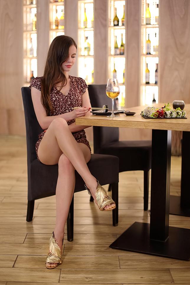 Bordowy kombinezon w kwiaty i skórzane złote sandały na szpilce