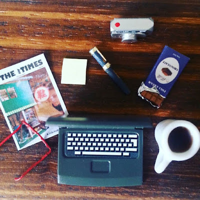 Flat lay of  a laptop,pair of reading glasses, magazine cover, pen and post it notes, digital camera, bar of chocolate and a mug of coffee.