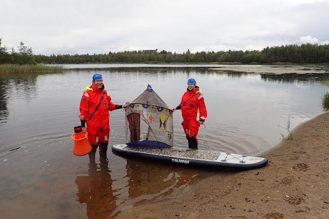 Kaksi ihmistä seisovat rantavedessä pelastautumispuvuissa, välissä SUP-lauta ja teltta.