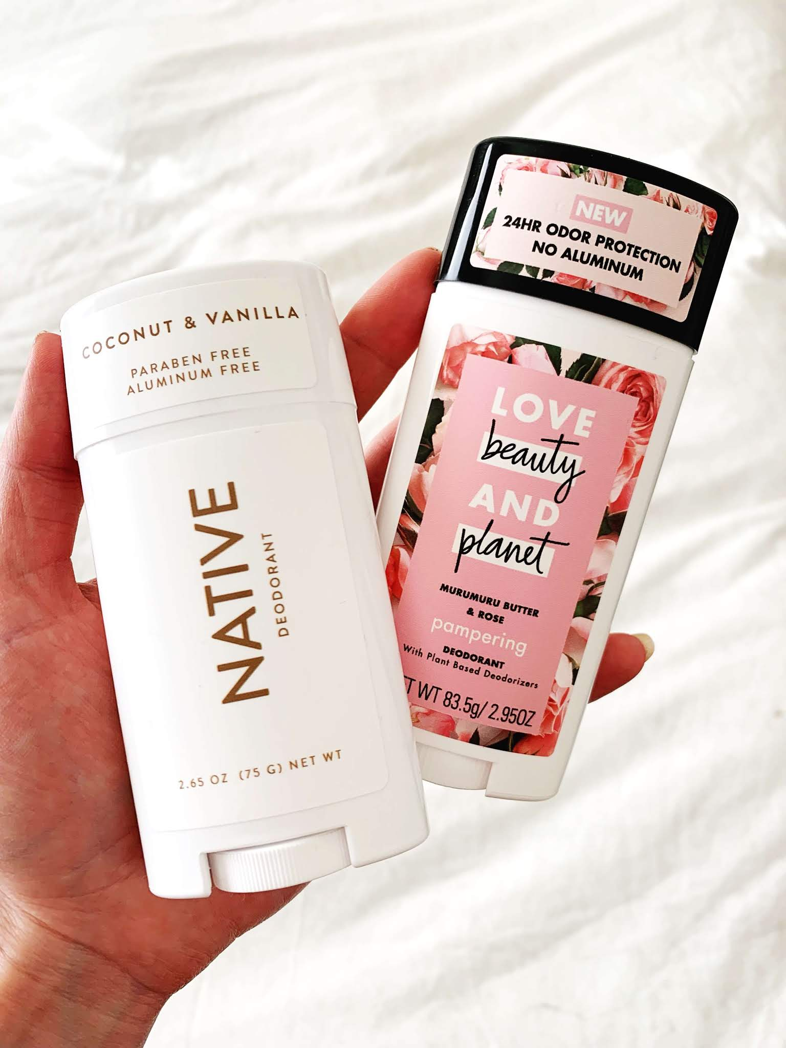 Hand holding Native and Love Beauty & Planet natural deodorant sticks