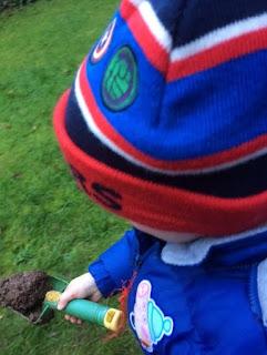 Little boy carrying soil on a trowel