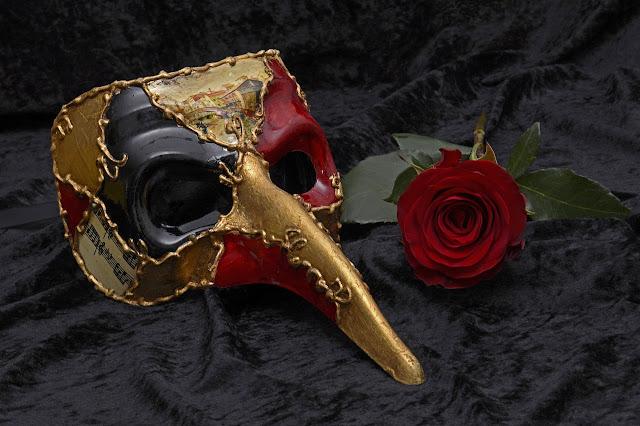 Maska teatralna i czerwona róża na czarnym tle