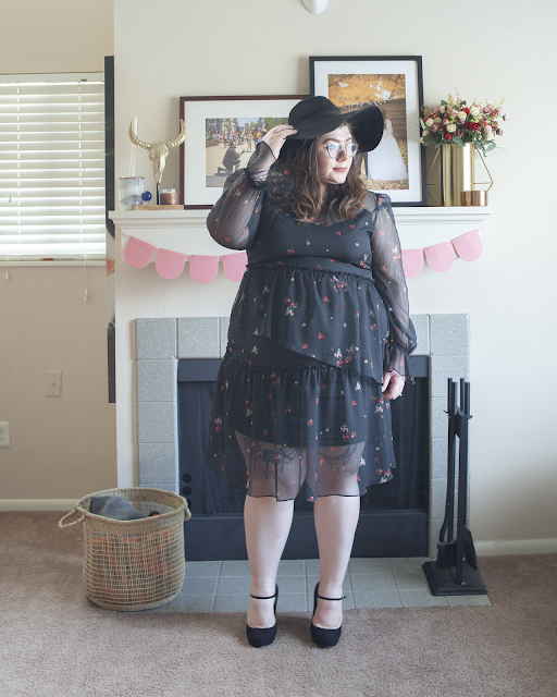 An outfit consisting of a black wide brim floppy hat, a microfloral on black sheer midi dress and black Mary Jane heels.