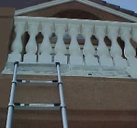 A ladder is used to reach the second floor cement balcony