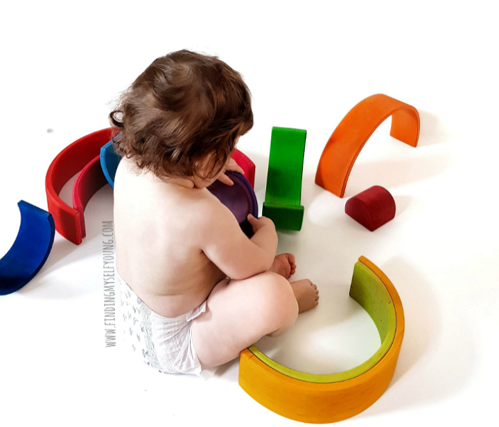 Baby stacking grimms rainbow pieces
