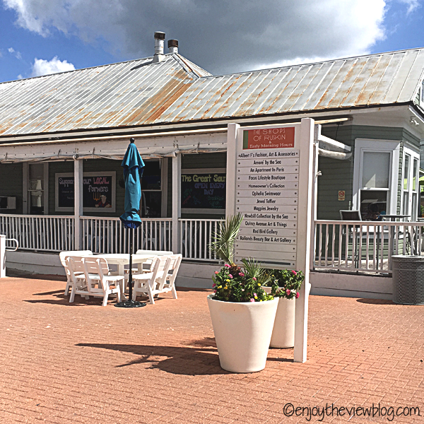 A side view of The Great Southern Cafe in Seaside - wooden building with a tin roof, wrap-around deck with seating, and the brick courtyard with seating that leads to the restaurant
