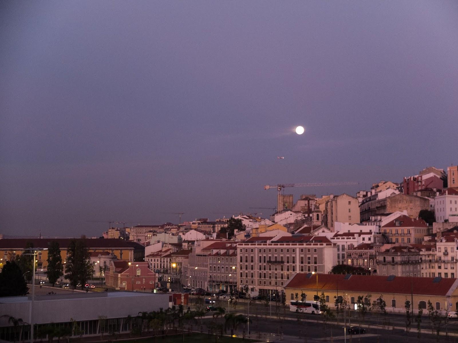 Moon glowing above Lisbon at dawn.