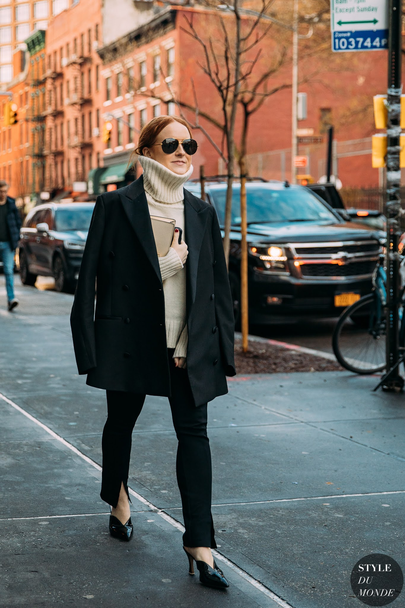 Libby Page Street Style Fall and Winter Outfit Idea With Chunky Turtleneck Sweater, Blazer, Ankle-Slit Pants and Mule Heels