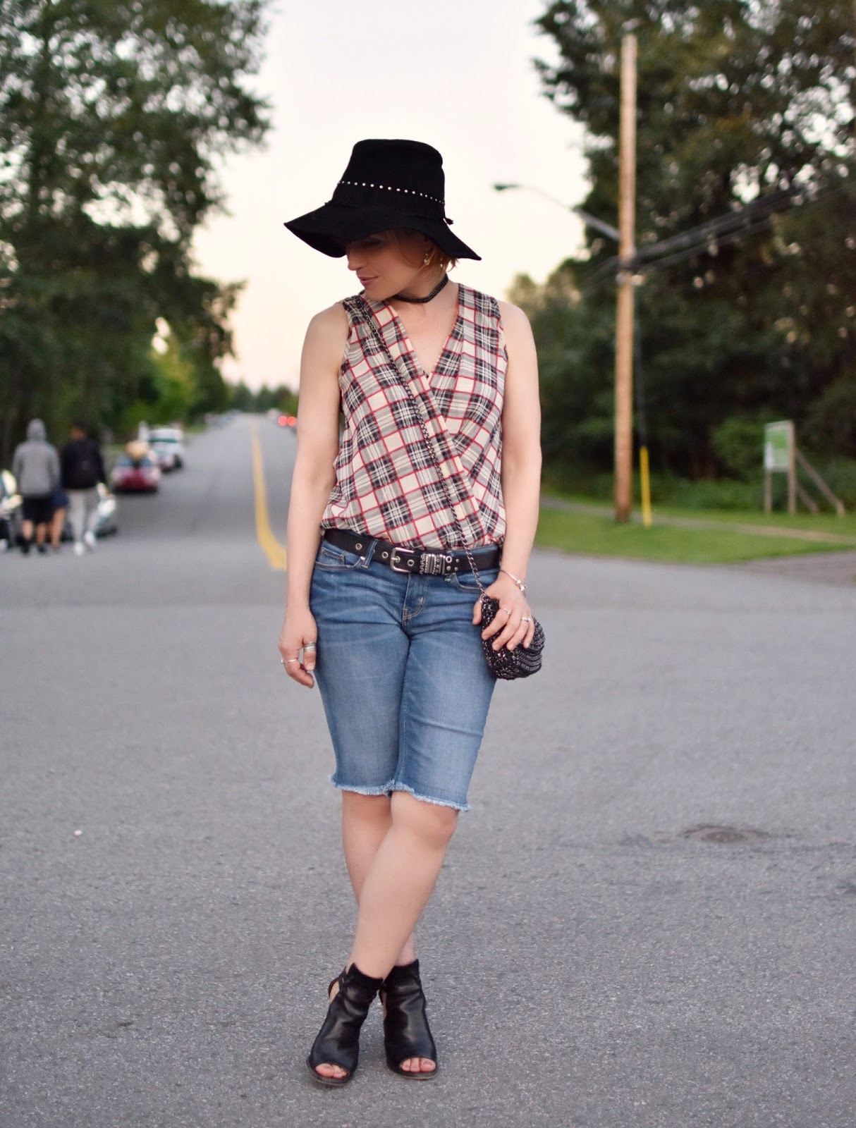 styling boyfriend shorts with a sleeveless plaid shirt, cut-out booties, and a floppy suede hat