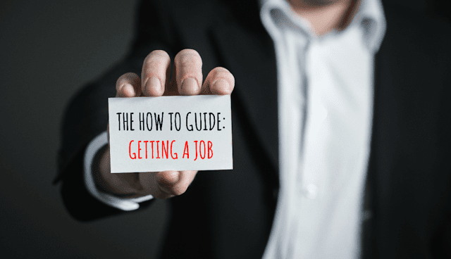 Man wearing a suit and holding a card that says how to guide: getting a job