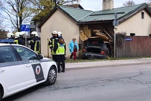 Ugunsdzēsēji skatās uz auto, kurš izbrauca cauri mājas sienai